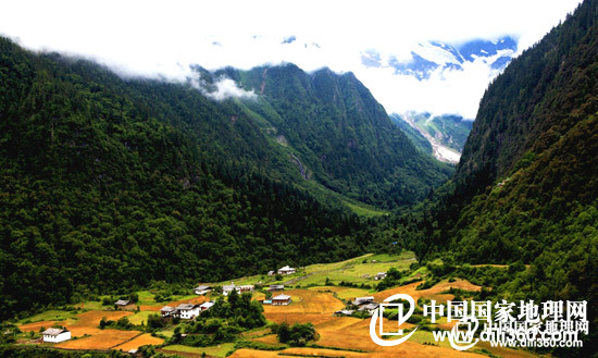 玩遍中国    整个下雨崩坐落在三角形的坝子上,群山像圈椅一样把小村